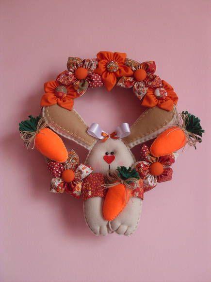 Guirlanda de palha revestida com juta.Decorada com coelho e cenoura de feltro,e flores de tecido. R$ 55,00
