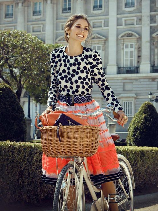 Oh so whimsical Olivia Palermo on a bicycle, wearing a printed top and skirt.