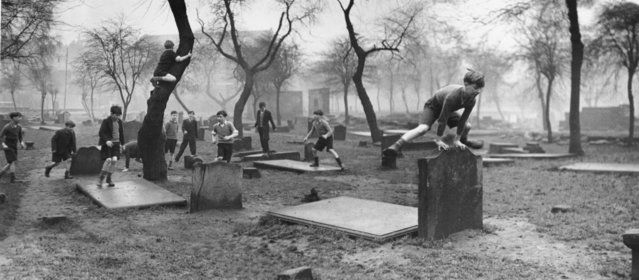 A group of boys from the Gorbals play amongst the gravestones of the Corporation Burial Ground in Rutherglen Road, UK, one of the few areas of greenery in the district, 1948.