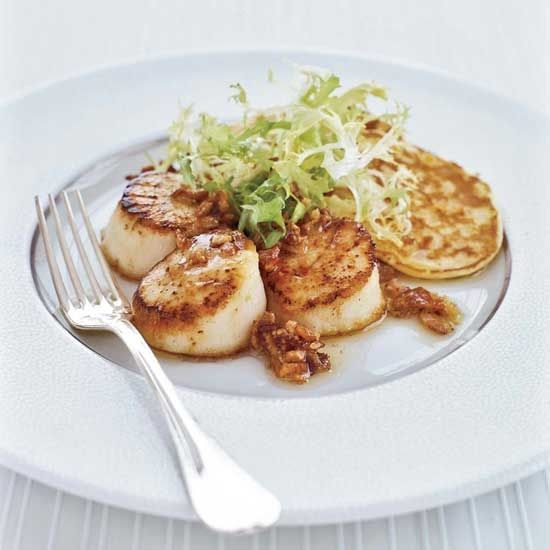 "Seared Scallops and Corn Cakes with Bacon Vinaigrette | Stewart Woodman often serves savory waffles and pancakes with his dinners in place of rice or potatoes. Here, he pairs big, beautifully seared scallops with delectable corn pancakes. ""Perhaps the reason is my dyslexia,"" he jokes. ""My wife, Heidi, thinks I see the world backwards—savory as sweet and vice versa."""