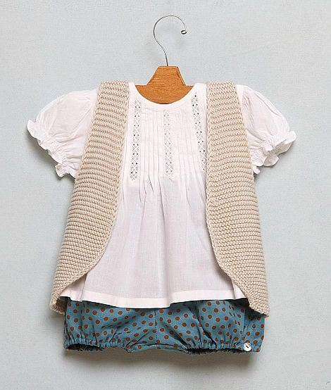 Look infantil, colete de tricô com blusinha branca manga bufante.