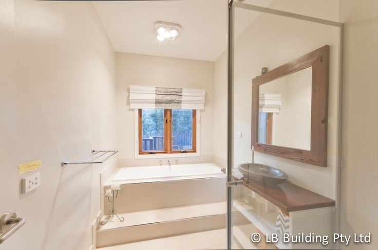 Bathroom design ideas. Timber windows opening onto outside decking. Recycled red gum mirror and vanity top taken from old fence posts on the owner's property. Handcrafted by LB Building.