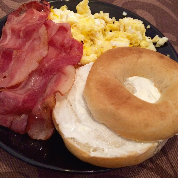 Brunch: scrambled eggs, fried bacon and bagel whith cream cheese