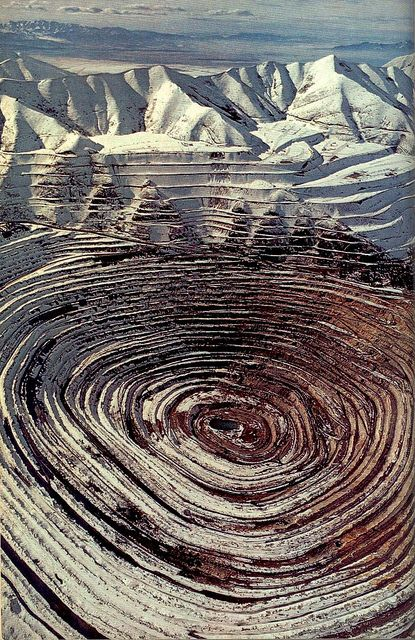 """Kennecott Copper mines bull's-eye in the Oquirrh Mountains stretches two and a half miles wide and more than half a mile deep - the nation's largest open-pit copper mine, and its most productive.""""    From article Utah's Shining Oasis by Charles McCarry, photographs by James L. Amos 1975"""