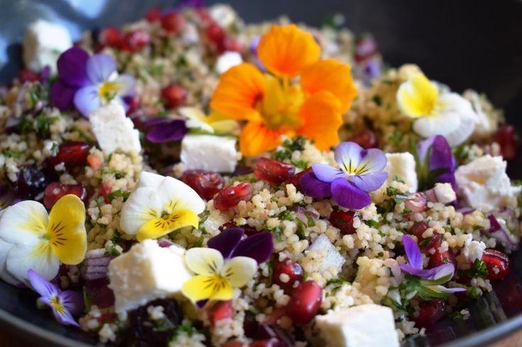 Deze couscoussalade met eetbare bloemen en kruiden zit vol kleur. Feta, pistachenoten, granaatappelpitjes, gedroogde veenbessen,... elke hap is een feest!