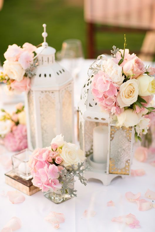 Centerpiece of White lanterns adorned with Hydrangea, Rose, Garden Rose, Lisianthus and Foliage e