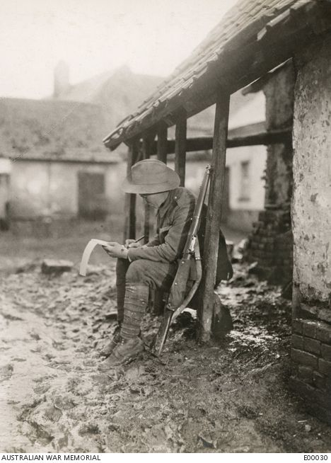 """A member of the 2nd Battalion """"carrying on"""" with his correspondence."""