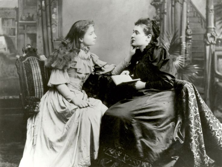 Anne Sullivan reads a book to Helen Keller as she 'listens' by touching Sullivan's lips to feel the vibrations of Sullivan's word. c.1894. [[MORE]] Source