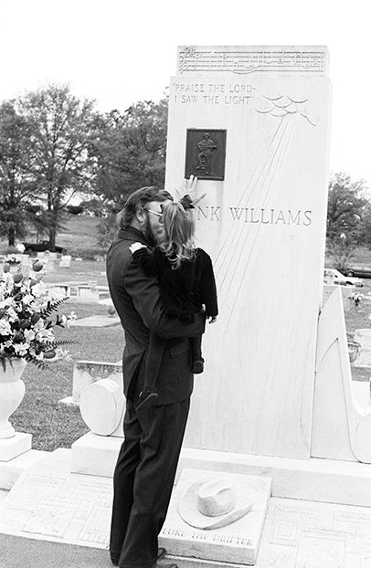 """Photo Credit: © Marty Stuart. """"Baby, your Grandpa was a man named Hank Williams,"""" Hank Williams, Jr., and his daughter, Katie, 1995. Archival pigment print."""