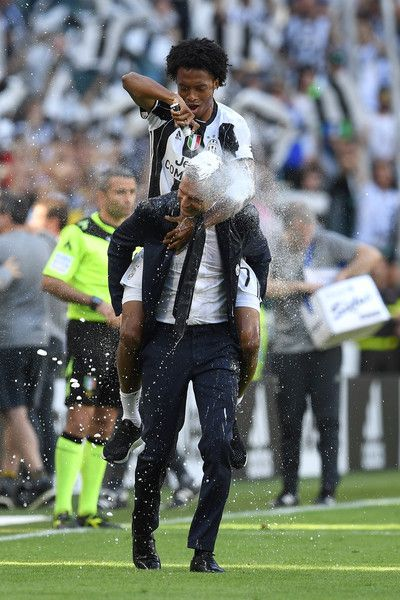 Juan Cuadrado and head coach Massimiliano Allegri of Juventus FC celebrate after beating FC Crotone 3-0 to win the Serie A Championships at the end of the Serie A match between Juventus FC and FC Crotone at Juventus Stadium on May 21, 2017 in Turin, Italy.