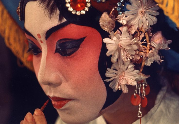Close-up of a Chinese actress wearing theatrical makeup applying red lipstick and wearing a cap with floral and jewel decorations / Digital Archive of Chinese Theater in California [1983?] (issued)
