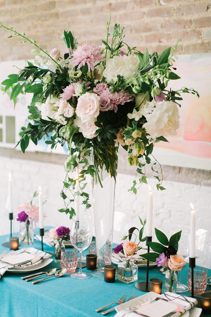 Elevated tall centerpiece design with garden roses, tulips, mums, anemone on a centerpiece table with teal tablecloth by Michelle Edgemont Design