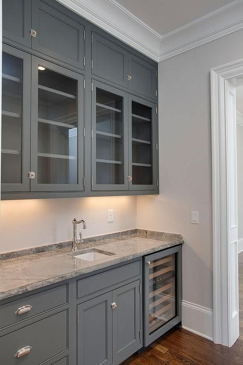 Grey Butler Pantry Features Glass Front Upper Cabinets And