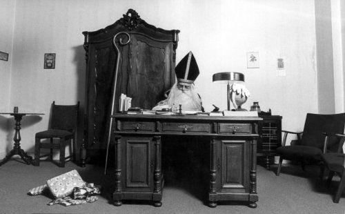 Sinterklaastijd: Sint Nicolaas (Sinterklaas) achter bureau, kado's op de grond, staf tegen een kast. [1973].