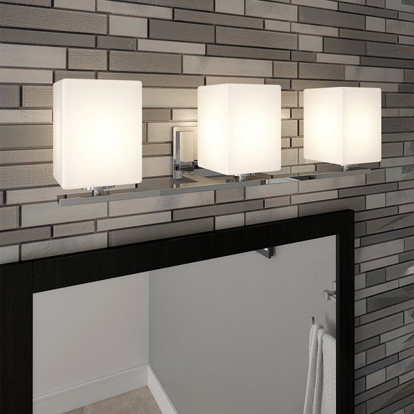 This wall light is cylinder shaped with square details. Constructed of formed steel with a polished chrome finish and frosted glass, this 3-light wall mount adds a modern accent to your home. This light's petite design mounts seamlessly to the wall without a chain or visible wires. This vanity light features a detailed steel trim to add elegance in any room or entry way. This fixture uses (3) 60-watt medium base incandescent bulb. This wall mount is UL listed, CUL listed and suited for da...