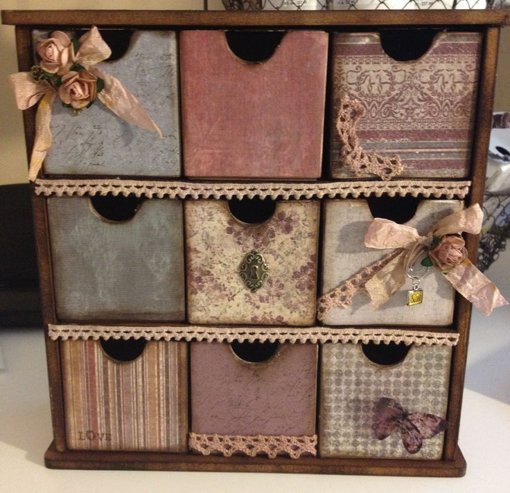 Este hermoso mini cajonera está listo para guardar todos tus tesoros. Es hechos a mano utilizando adornos y trabajos de calidad. El marco está hecho de madera y cada cajón está hecho de tablero de viruta gruesa y cubierta con cartulina. Es mano enarenada y entintado. Los encajes y las flores son teñido a mano. El pecho mide unos 9 ½ x 8 ½. Los cajones miden aproximadamente 2 x 2. Esto sería una adición perfecta para cualquier habitación.