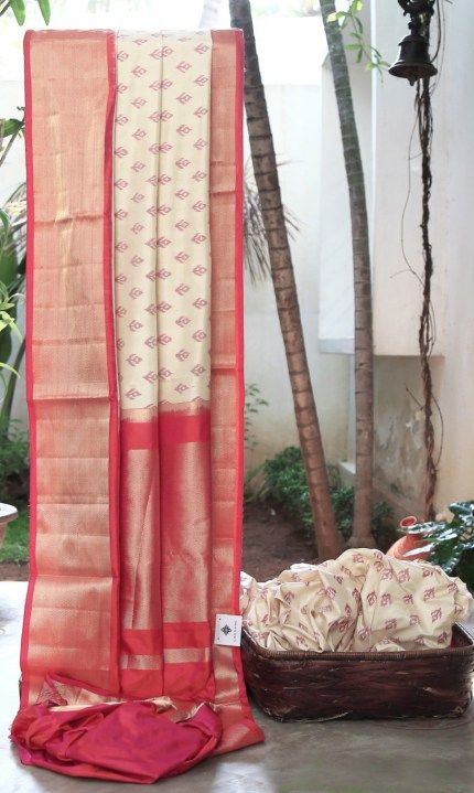 LUSTROUS OFF-WHITE IKKAT SILK WITH PURPLE BHUTTAS INTRICATELY WOVEN ALL OVER. THE ORANGE-PINK BORDER AND PALLU WITH GOLD GIVES THE SAREE A SPECTACULAR FINISH