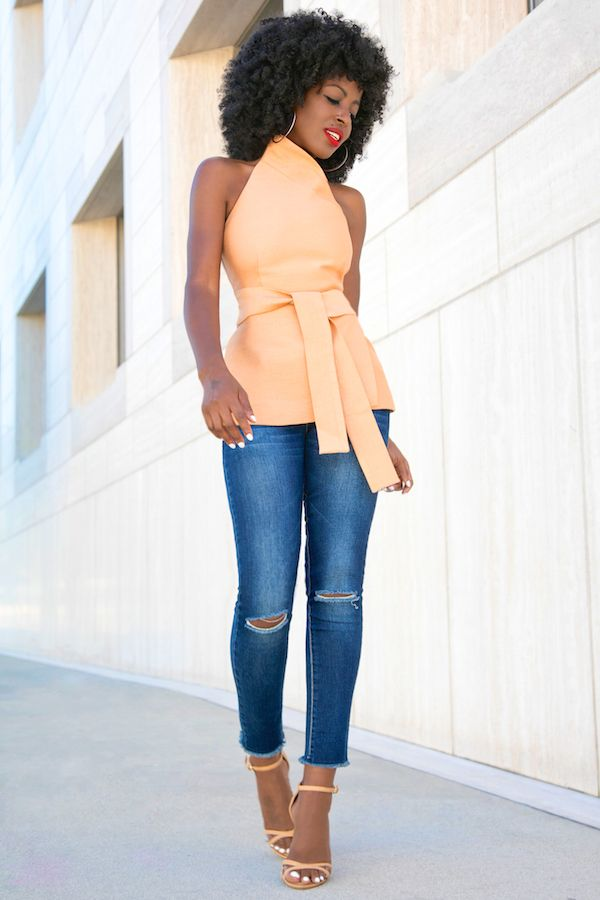 Asymmetric Wrap-Around Halter Top + Ankle Length Jeans. The soft peach and faded denim go well with her skin color. It emphasises her waist and figure.