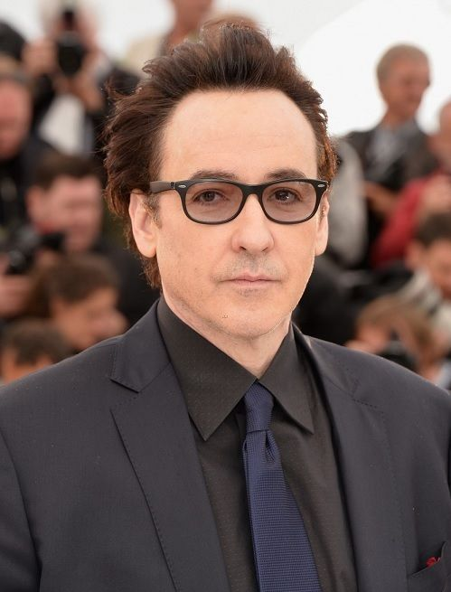 John Cusack wearing Ray-Ban Liteforce style RB4207 601S/9A with prescription lenses while attending the Cannes Film Festival