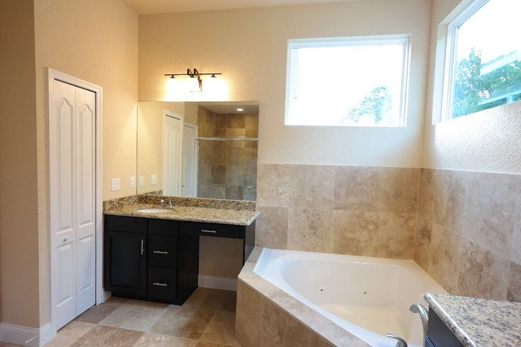 The master bath features granite countertops his and her for Oversized garden tub