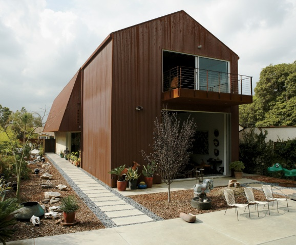 Constructed of corrugated Cor-Ten steel, the house echoes the form and feeling of an industrial shed.
