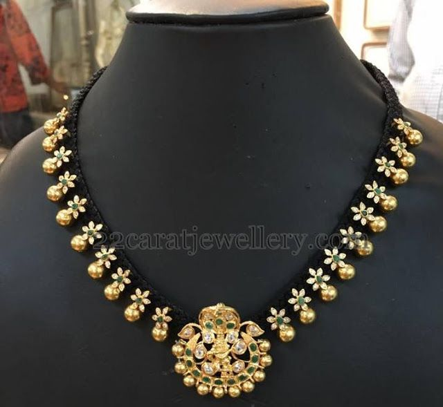 Black cord necklace with simple CZ and emerald stones studded floral motifs attached all over the set. Emerald studded Lakshmi embossed pe...