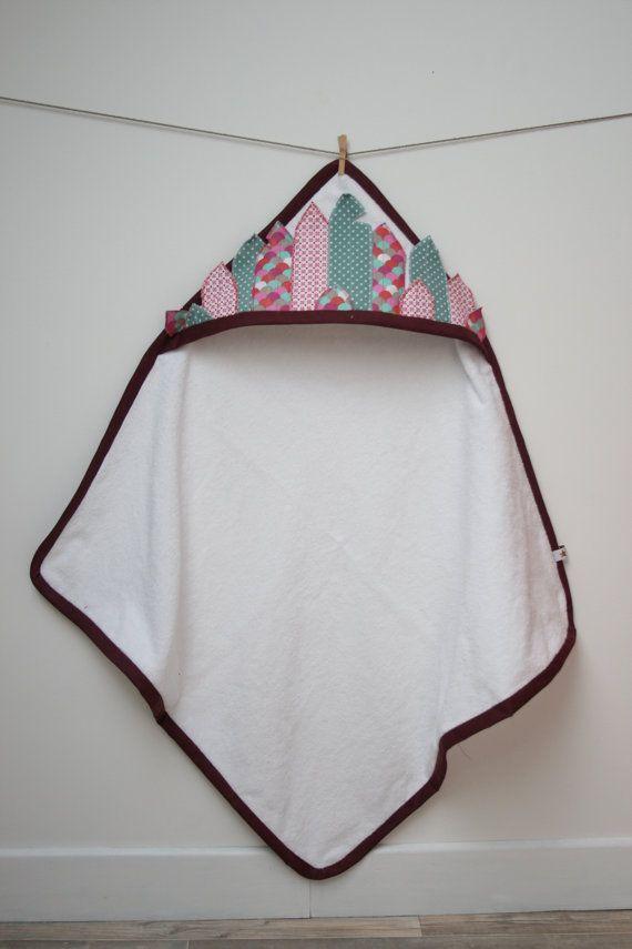 La sortie de bain  Ptite indienne  est réalisée en éponge blanche avec sur la capuche des plumes doublées et surpiquées de plusieurs couleurs : fleurs géométriques roses ; écailles roses, turquoises, vert amende, écrues, taupes, et un tissu vert deau à pois blancs. La cape de bain est finie par un biais pourpre.  Une sortie de bain originale dans lesprit ptit indien, idéale comme cadeaux de naissance.  Dimensions: carré de 67 cm x67 cm capuche : 44 cm x 20 cm  La version garçon  Ptit indien…