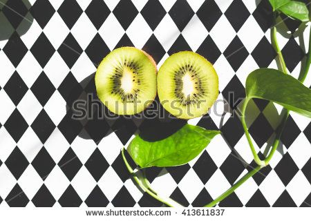 composition of slices of kiwi, purse and leaves on colored background - stock photo