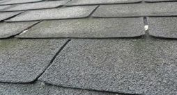 What causes roof shingles to curl up at corners?