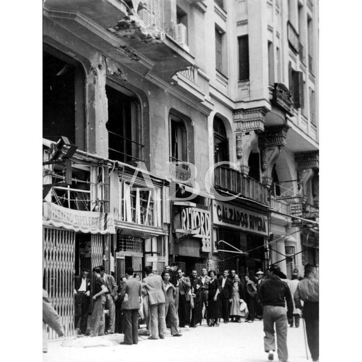 """Spain - 1936-38. - GC - UNA COLA DE TABACO EN PLENA """"AVENIDA DE LOS OBUSES"""", JUNTO A UN EDIFICIO CON IMPACTOS DE LA METRALLA."""