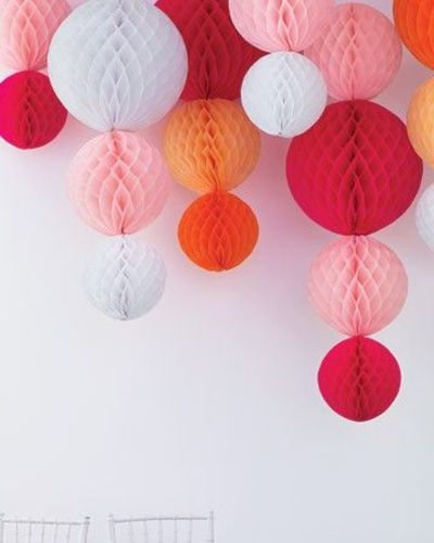 "paper ball ""chandelier"" using pre-made honeycomb tissue balls stapled to ribbon + hung from the ceiling. so clever!"