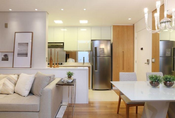 Sala de estar, jantar e cozinha integrada. Piso de madeira e porcelanato. Sofá claro com almofadas, mesa em laca branca, cadeiras com tecido em linho, armários inferiores amadeirados, e superiores com vidro branco, geladeira inox, espelho na cozinha, porta com guarnição até o teto. Iluminação embutida na cozinha e sala. Salas e cozinha decorada, decoração. Reforma e decoracao apto completo