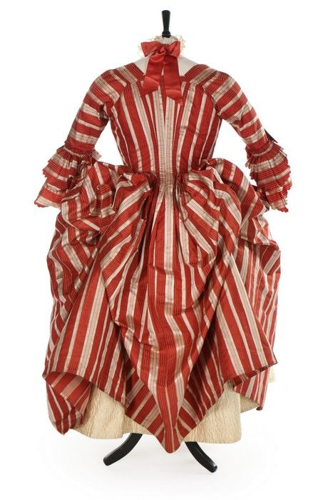 A fine striped robe à la polonaise, French, 1770s. of cinnamon and ivory satin stripes, with double engageants, English back, the interior with tapes and loops to form polonaise folds; with ivory satin stomacher covered with pinked ribbon rosettes; and a finely quilted ivory satin petticoat with overall lattice design and flowerheads within triangles to the hem; together with a modern choker made to match from Valenciennes lace and ribbon