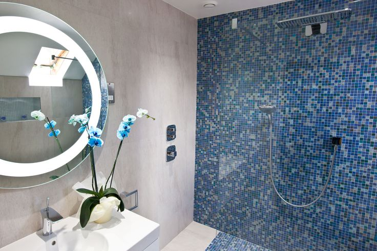 Boutique spa inspired bathroom featuring ocean blue mosaics and a striking mirror. Copyright The Designer Knowledge. Photo by Ani Evans Photography.