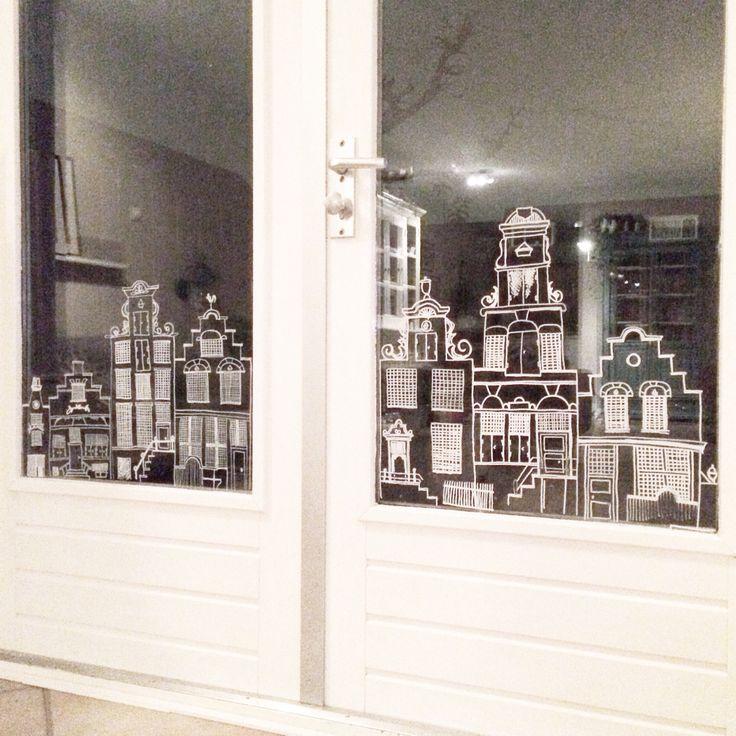 Huisjes op het raam getekend met krijtbordstift