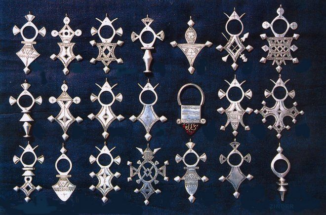 Africa | A collection of Tuareg Crosses. Niger. | Tuareg crosses, now worn by women as pendants around the neck, were originally worn by men, passed down from father to son when the boy reached puberty | Most of the cross designs are named after oasis towns or mountains between Agadez in Niger and the Hoggar Mountains in the north, with the Agadez (Tuareg capital) being the best known of all the crosses.