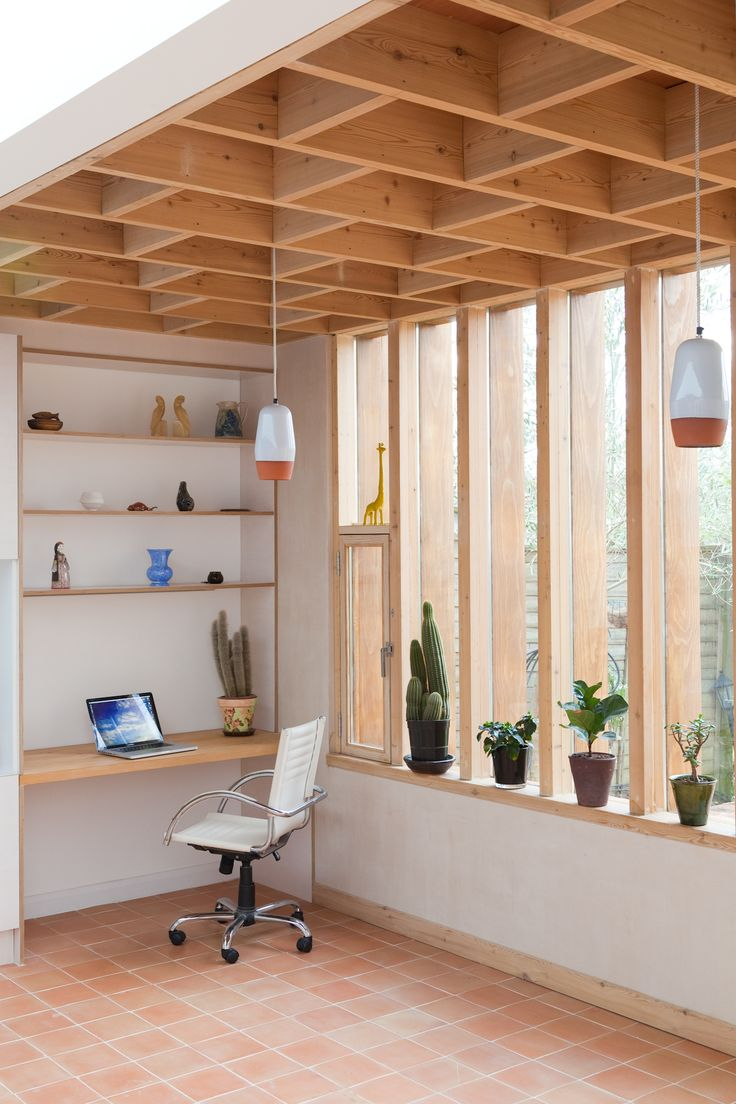 Louvre windows afford privacy from surrounding buildings. Internally earthy tones connect the interior to the garden.