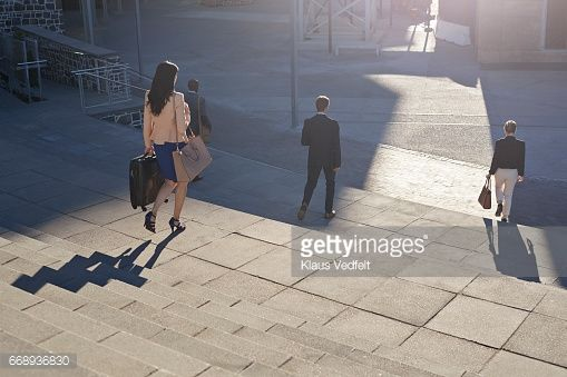 Stock Photo : Group of businesspeople walking on staircase with phones and bags