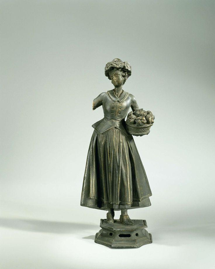 Anonymous | Figuur, voorstellende De Lente, Anonymous, c. 1700 - c. 1800 | Figuur, vrouw met bloemen om het hoofddeksel en een mand met vruchten en bloemen (De Lente). Op een opengewerkt laag voetstuk.