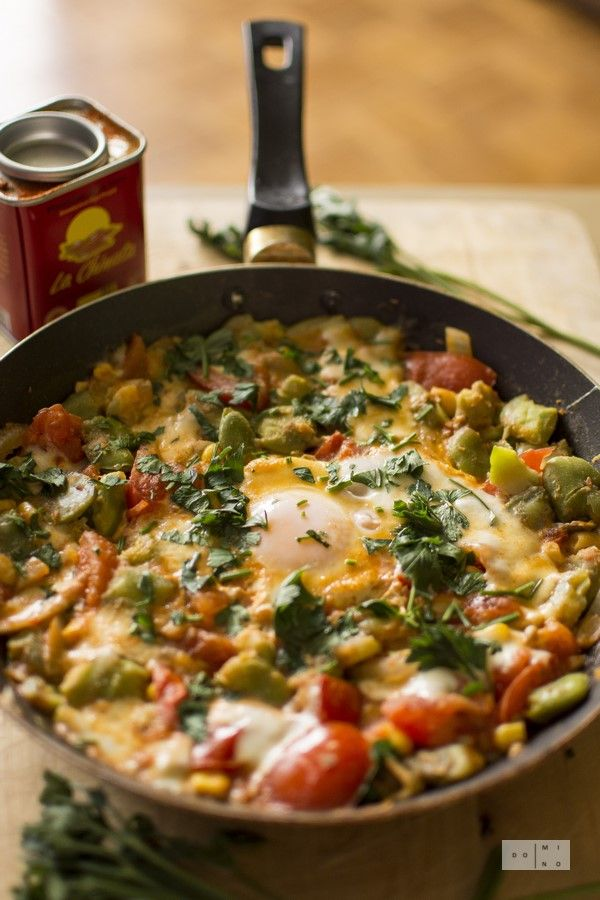 Splendid shakshouka with fava beans, corn & mozarella. Perfect, nutritious breakfast. Eggs and tomatoes with fava beans, mozarella and corn.