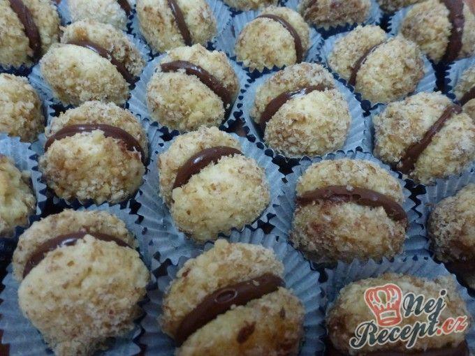 Křupavé ořechové cukroví plněné čokoládovým krémem Těsto: 350 ghladká mouka 200 gmargarín nebo máslo 150 gkr. cukr 1 ksvejce 2 ksžloutky špetkasůl 2 bal.vanilkový cukr 2 lžícerum 150 gmleté vlašské ořechy 2 ksbílky na vylepšení chuti citronová kůra Glazura: 100 ghořká čokoláda 40 gmáslo