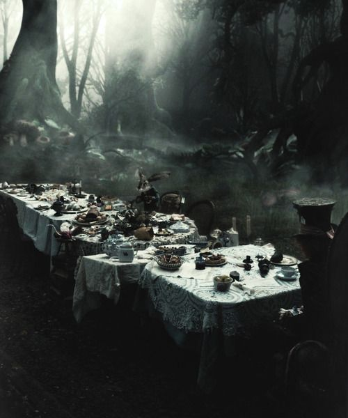 There was a table set out under a tree in front of the house, and the March Hare and the Hatter were having tea at it.