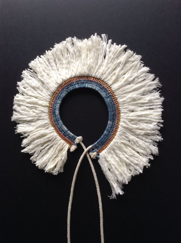 Woven rope necklace with tassel fringe.