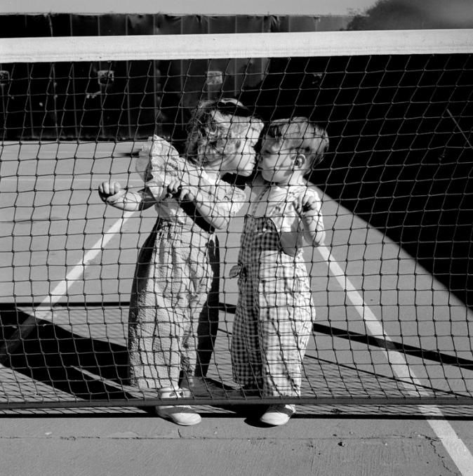 Vivian Maier, Two Children Kissing at tennis net, Los Angeles, 1955
