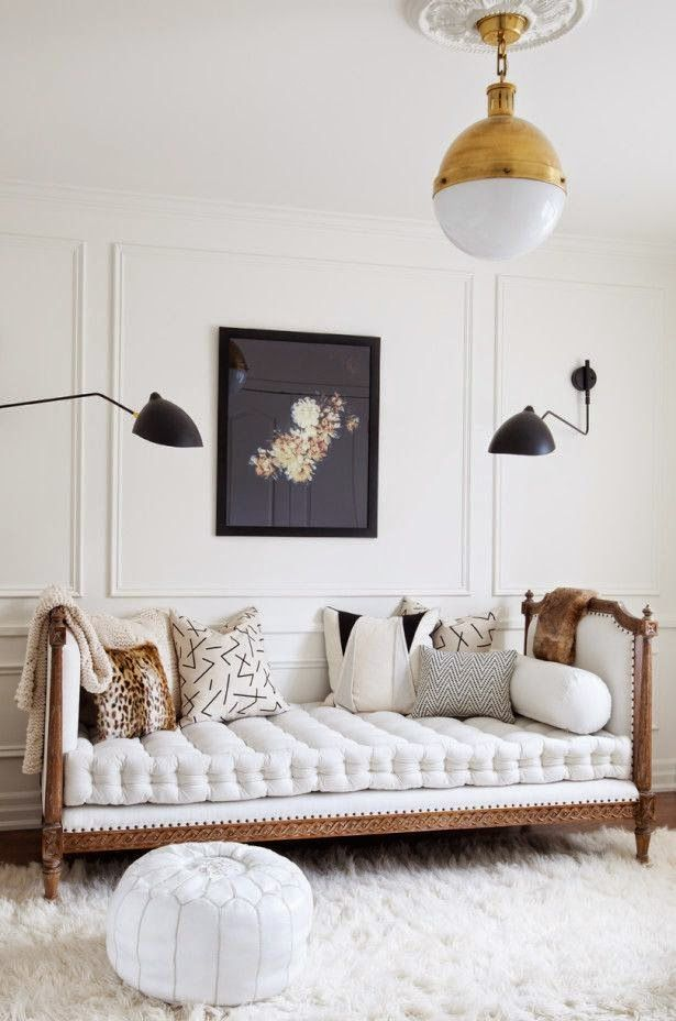 I love the antique gold light fixture paired with the tufted couch. The white fur carpet brings the whole room together with that modern eclectic feel.