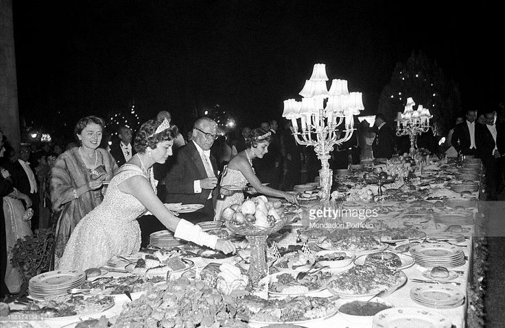 Italian politician and President of the Italian Republic Giovanni Gronchi, Her Imperial Highness Princess Soraya of Iran (Soraya Esfandiyari Bakhtiyari) and the princess Shahnaz Pahlavi, Shah's daughter from his first wife, helping theirself at the buffet in honour of the Italian guest in the grdens of Golestan Palace. Behind them, Italian politician's wife Carla Gronchi. Tehran, September 1957.