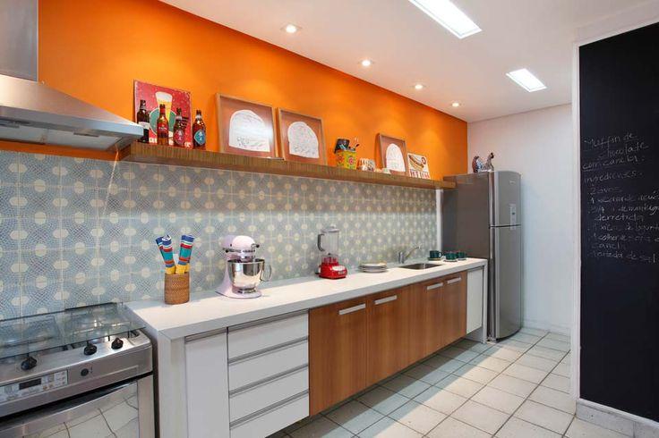 Cozinha com um destaque para a cor laranja, mas com móveis em madeira e MDF branco, parede de lousa e piso branco.