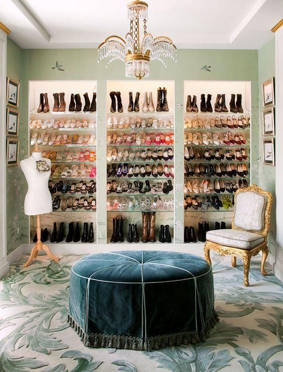 French walk-in closet features a brass and crystal chandelier illuminating a round blue French ottoman with tassel trim.