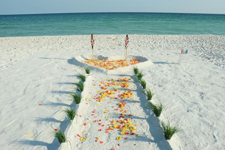 Rose petal aisle and Heart in the Sand with decorated tiki torches. Navarre, Florida destination beach wedding