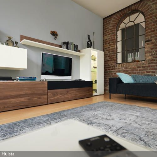 Das Wandteil in Ziegelstein-Optik verleiht dem Wohnzimmer ein uriges Ambiente. Der Fernsehschrank passt sich dem robusten Look an. Hängeregal, -schrank und Vitrinenschrank…